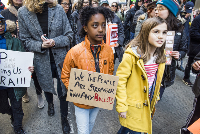 "New York City, NY, USA - March 24, 2018: Young African-American girl holding hand written sign reading ""We the people are stronger than any bullets"" at March For Our Lives 2018 demonstration"