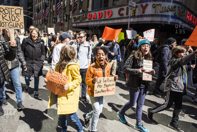 New York City, NY, USA - March 24, 2018: Group of people of all ages chanting as they walk past Radio City Music Hall during March For Our Lives 2018 demonstration