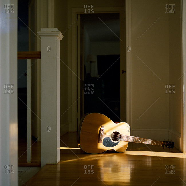 Acoustic guitar on floor in hallway