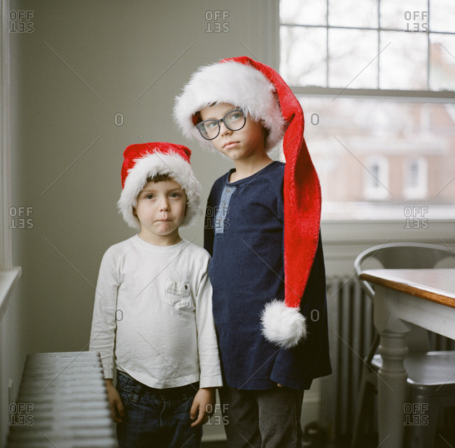 Two boys wearing long Santa hats