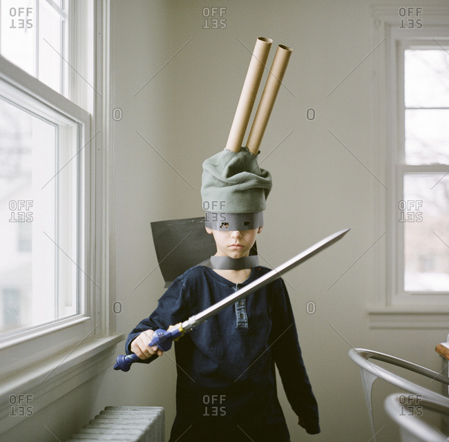Boy dressed up in a costume with a sword and a mask