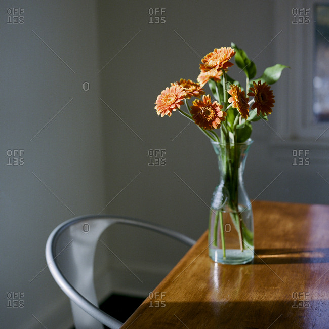 Glass vase filled with flowers on wooden table