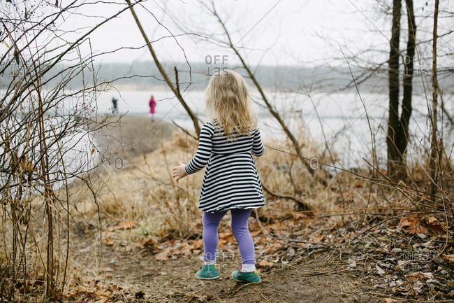 Rearview of little girl walking towards lake to join family