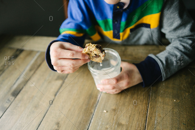 Young boy at kitchen table dunking cookie into glass of milk