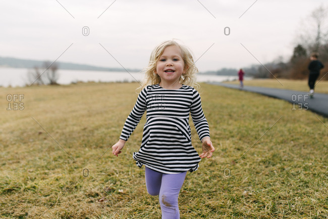 Little girl smiling running towards camera