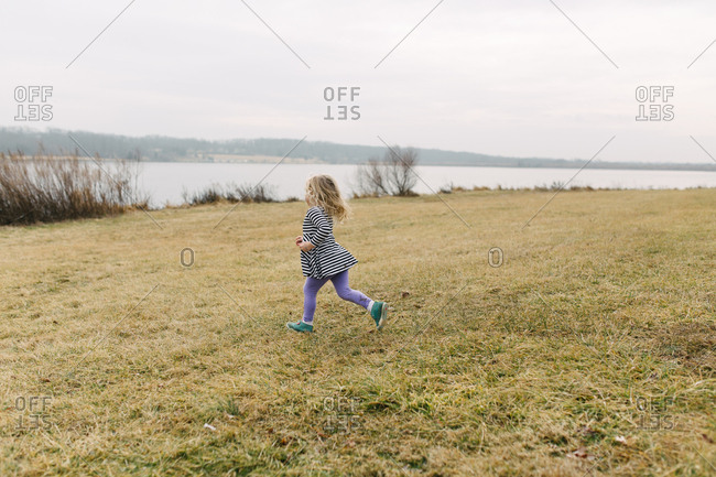 Little girl running towards water on lake side