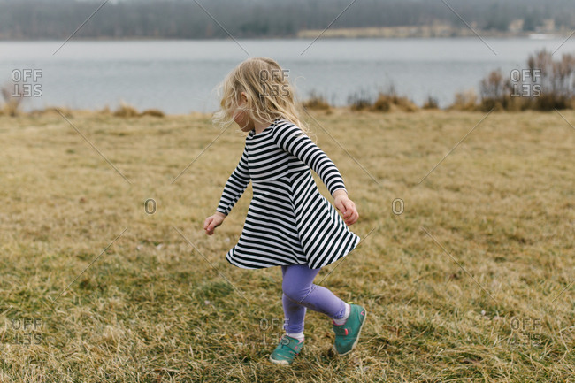 Little girl frolicking by side of lake