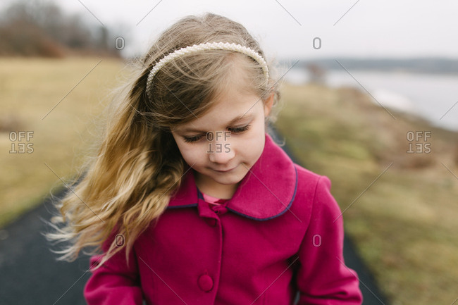 Portrait of young girl deep in thought walking by side of lake