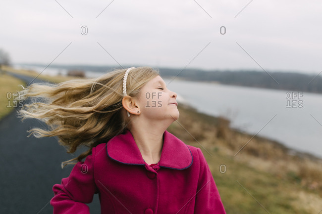 Young girl tossing head in wind by side of