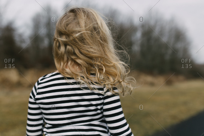 Rearview of little girl with windblown hair on wintery afternoon