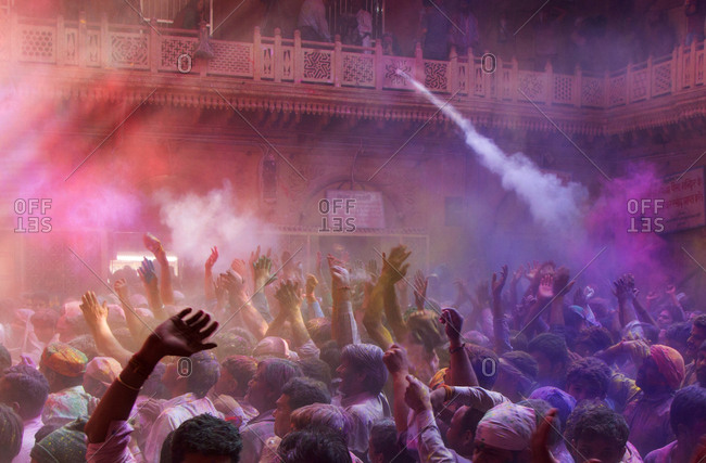 Vrindavan, India - March 05, 2015: Clouds of colored powders envelop revelers during the holidays festival in Banke Bihari temple