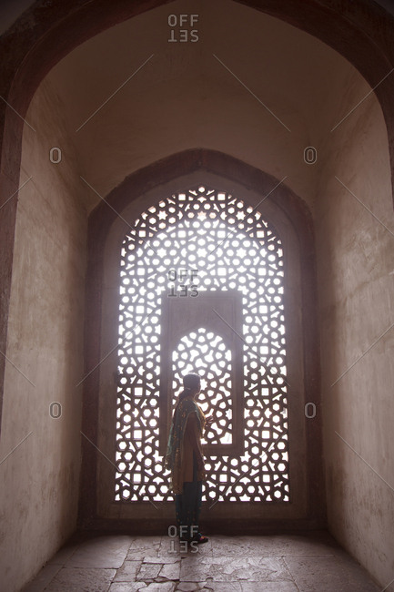 New Delhi, India - March 07, 2015: Sun filtering through lattice work in window lighting tourist visiting tomb of Emperor Humayan
