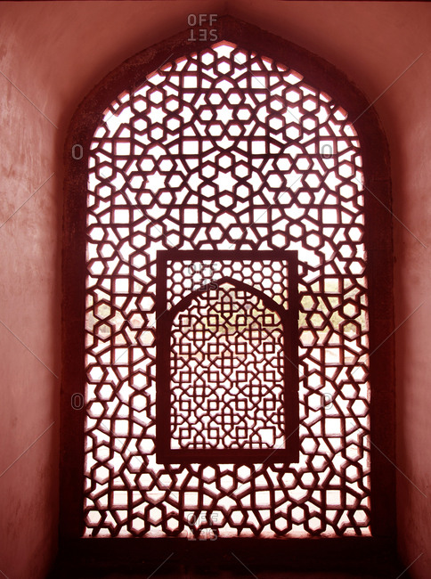 New Delhi, India - March 07, 2015: Light filtering through lattice work in symbolic niche facing Mecca at tomb of Emperor Humayan