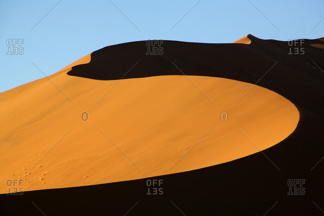 Sensuous curves of sand lit by desert sun in Namibia