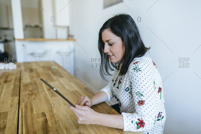 Woman sitting at kitchen table in pajamas checking news on tablet computer