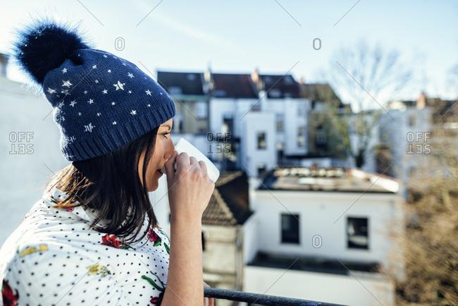 Woman wearing beanie enjoying cup of coffee on balcony on winter morning