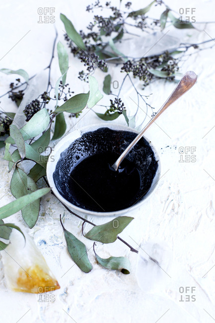 High angle view of bowl of Maca Charcoal Mask on plaster background