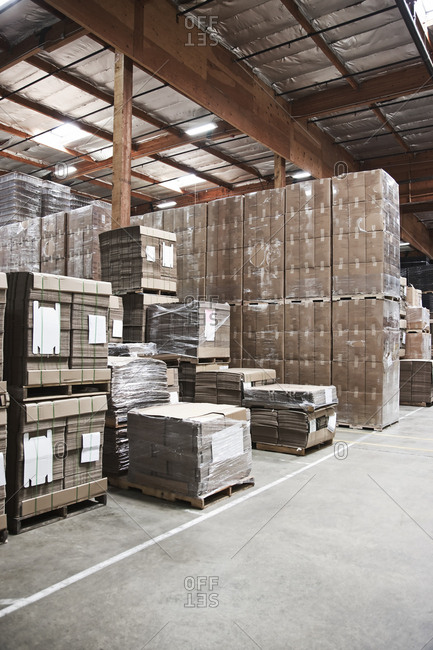 Warehouse interior showing stacks of cardboard used for packaging.