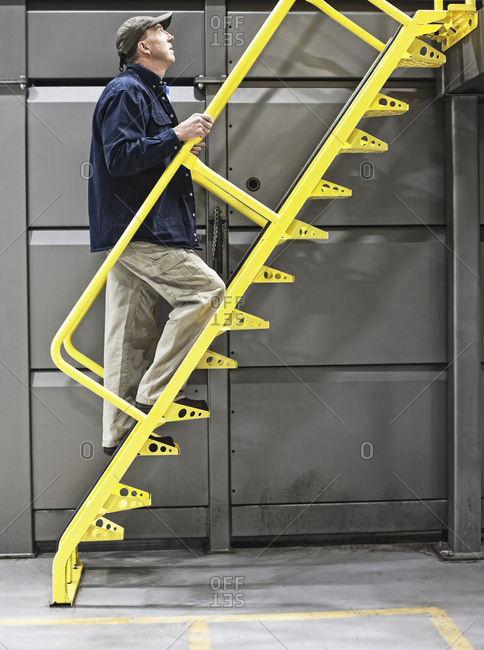 Warehouse worker climbing a metal staircase in a warehouse facility for bottled water.
