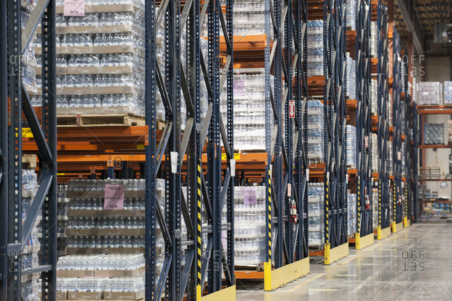 Interior of a warehouse showing flavored bottled water stored on pallets and set on large racks.