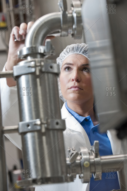 Caucasian female technician wearing a head net and checking large stainless steel processing tanks in a bottling plant. that makes flavored bottled water.