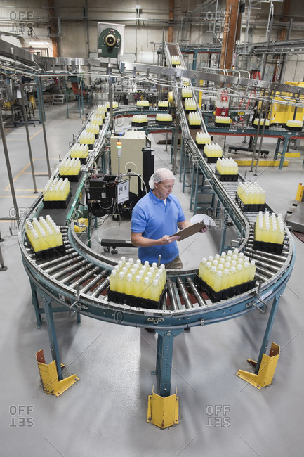 Caucasian male wearing a head net and checking inventory next to a conveyor belt of lemon flavored water in a bottling plant.