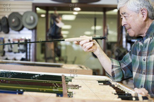 Asian American senior male checking the balance on a 5 weight fly fishing rod for sale in a fly-fishing shop.