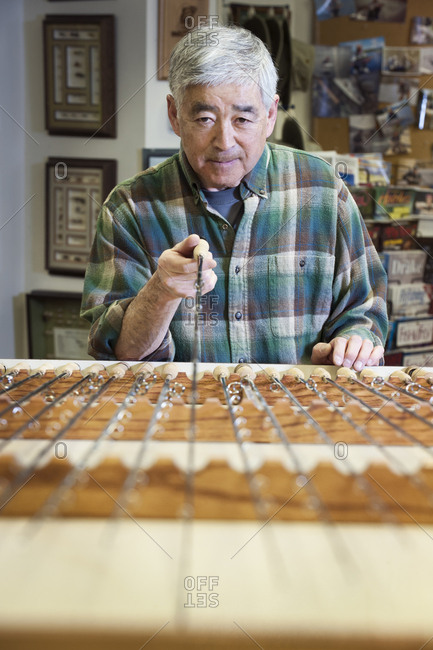 Asian American senior male checking the balance on a 5 weight fly fishing rod for sale in a fly fishing shop.