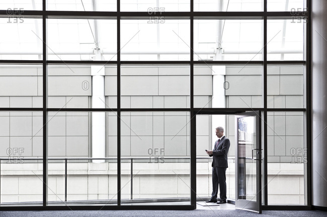 Businessman on a small office balcony checking his phone.