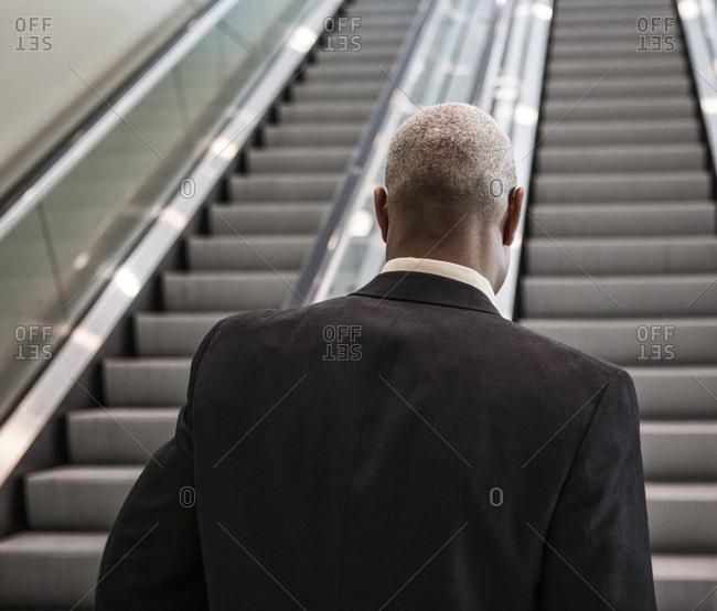 Black businessman on his way up an office escalator.