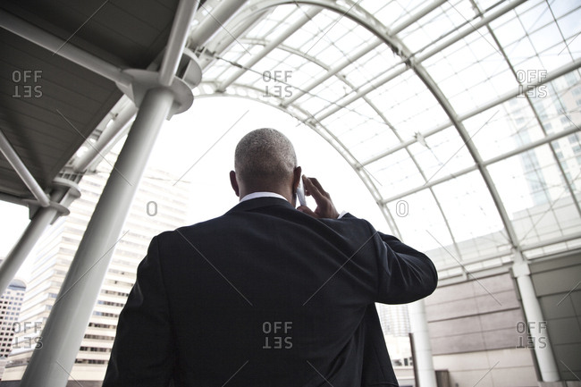 Black businessman on the phone while walking through a large glass covered walkway.