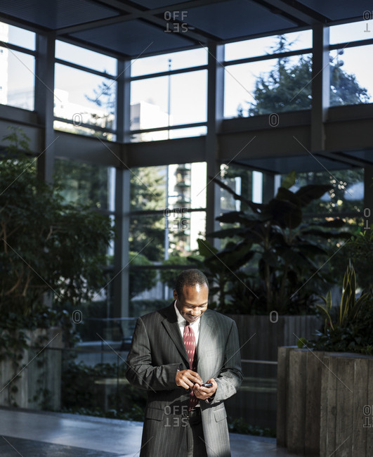 Black business man texting in a large lobby waiting area.