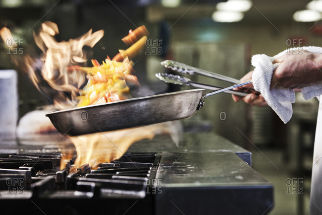 Close-up of chef's hands holding a saute pan to cook food, flambeing contents. Flames rising from the pan.