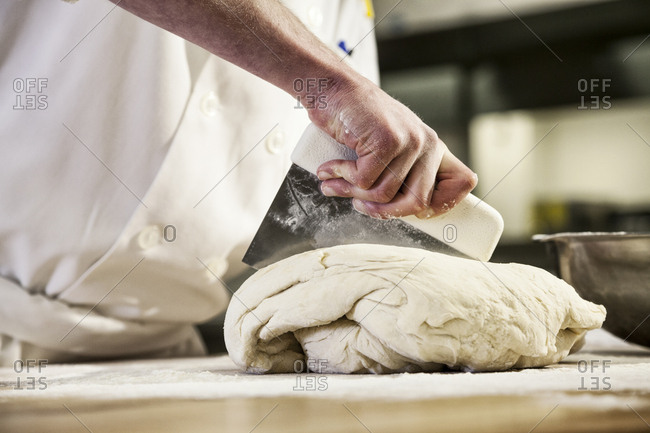 A chef dividing up bread dough into sections on a floured worktop.