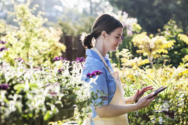 Caucasian woman employee of a garden center nursery texting in an order for new plants.
