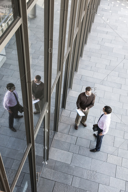 View from above of two businessmen meeting outside of a building next to a bank of windows.