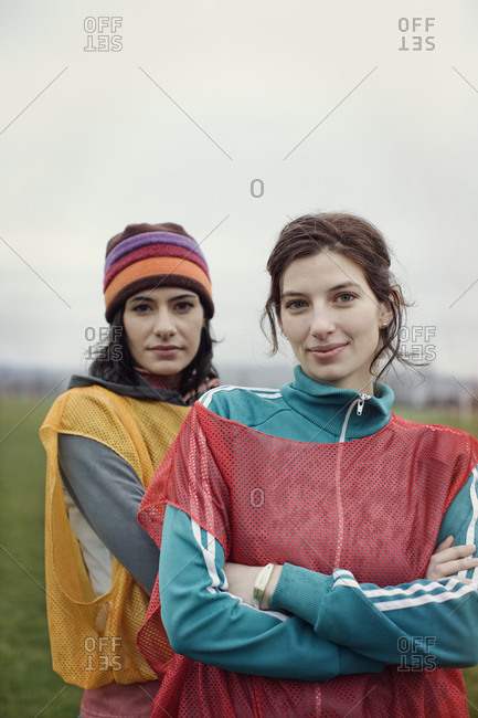 Portrait of two Caucasian women in sports clothing with team bibs of opposing teams and woolly hats side by side.