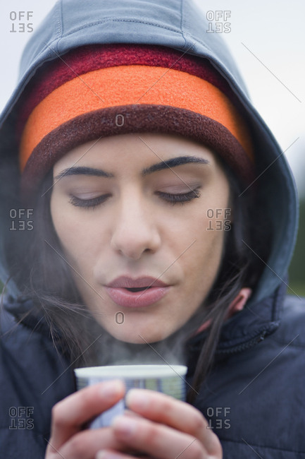 Caucasian woman blowing on the surface of a hot cup of coffee on a winter day.