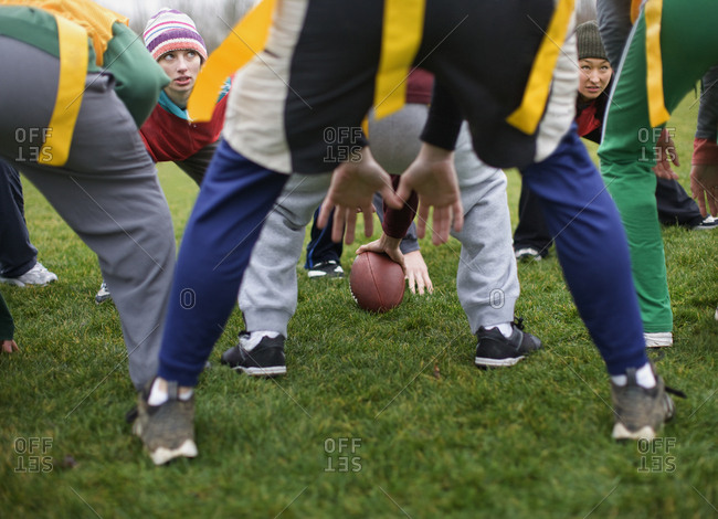 Close up of mixed team members at the line of scrimmage, playing non-contact flag football.  One player holding the ball.