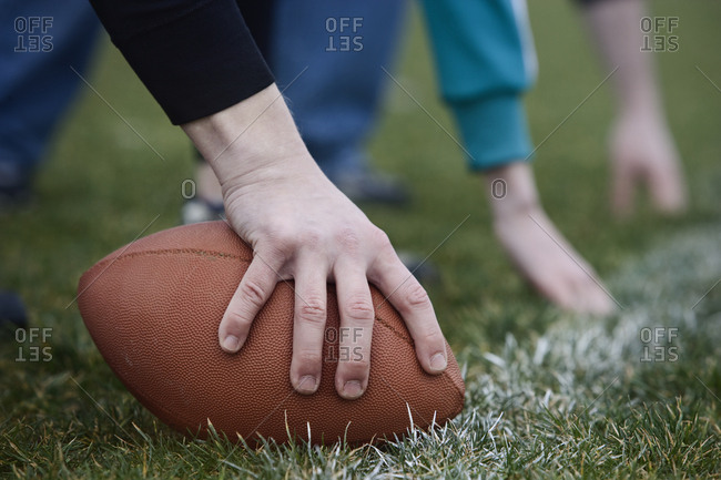 Close up of a hand holding an oval football on the line, during a game of non-contact flag football.