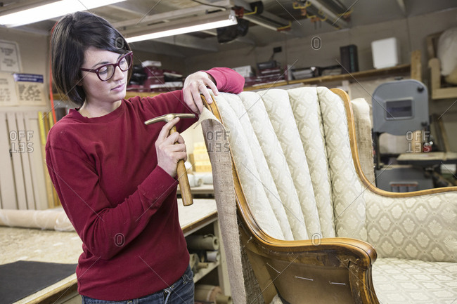A young female upholsterer using a tack hammer on a chair in an upholstery shop.