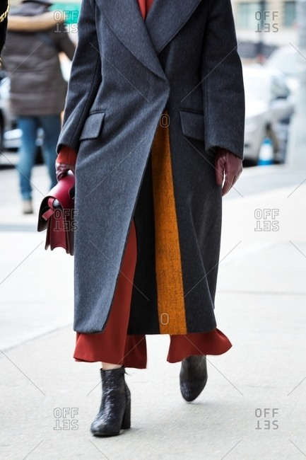 Woman wearing long grey coat with orange stripe carrying red leather handbag