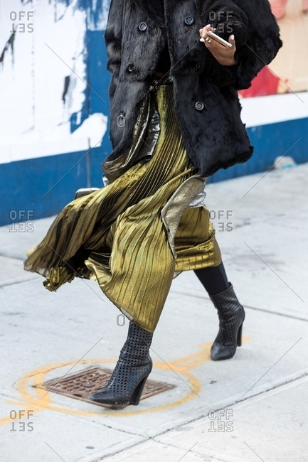 Woman wearing metallic pleated chiffon skirt and faux fur coat striding down the street