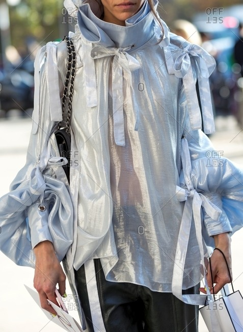 Woman wearing metallic chiffon blouse with puff sleeves and bows with leather pants