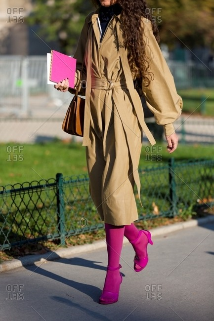 Woman wearing magenta ankle strap heels with matching tights and long camel coat belted at waist