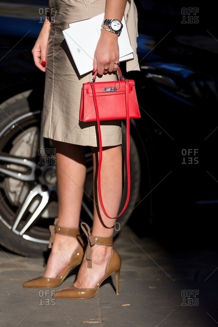 Woman wearing brown patent leather ankle strap heels carrying Hermes Kelly mini handbag