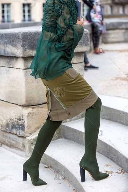 Woman climbing stairs wearing forest green high boots with olive zippered skirt and chiffon blouse