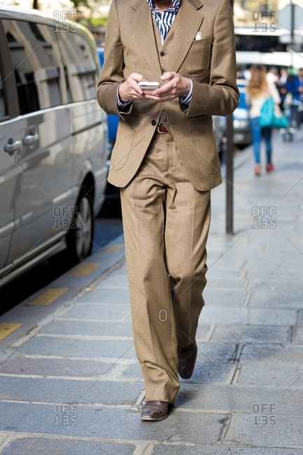 Person walking texting on phone wearing three piece beige suit