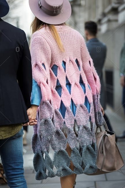 Rearview of woman wearing graduated open knit poncho