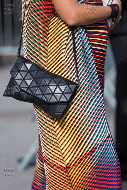 Woman wearing multicolored geometric print dress carrying handbag with triangular quilting